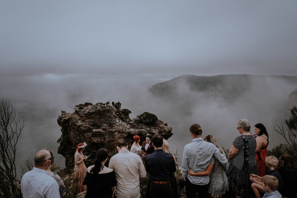 Two brides elope on a foggy day on a cliff in the Blue Mountains