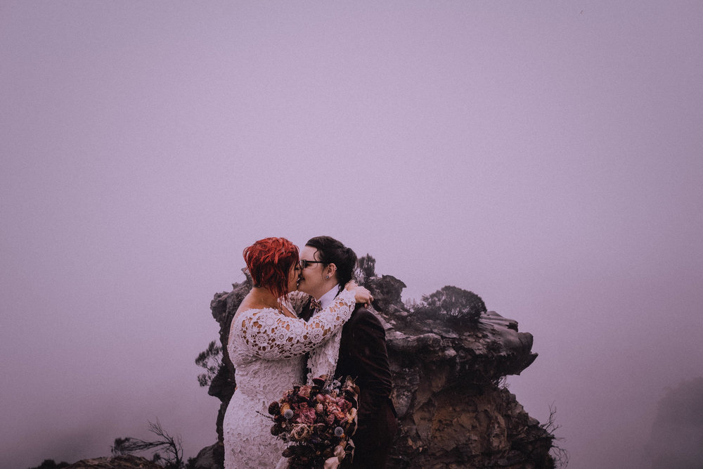 Two brides get hitched at Boars Head for a stormy day cliffside elopement in Katoomba