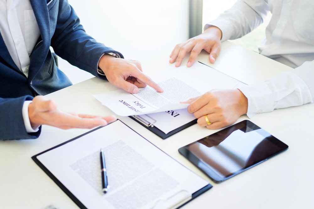 Two men discussing a claims adjustment document