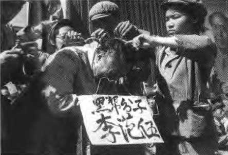 """Red guards force half-shaving a """"monster' who was their former teacher. A cardboard hanging from his neck with the text """"I was a monster."""""""