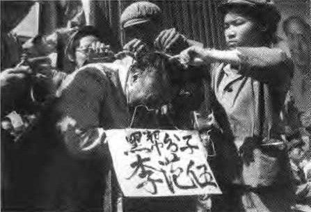 "Red guards force half-shaving their former teacher. A cardboard hanging around his neck with the text ""I am a devil."""