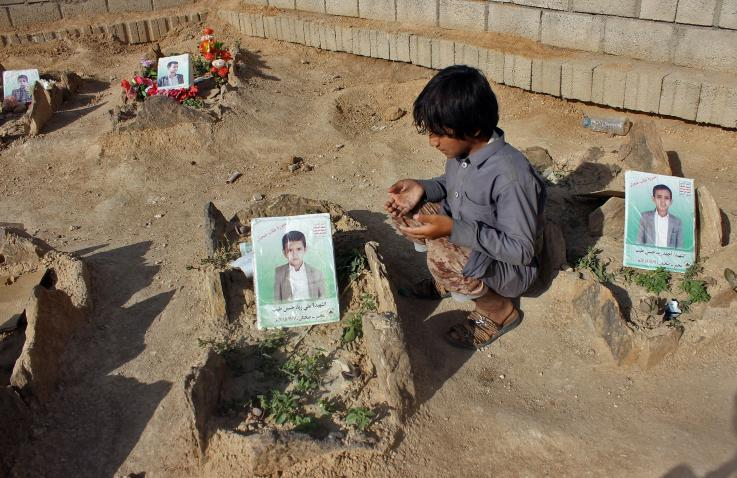 A Yemeni child prays by the graves of students who were killed by a Saudi-led coalition airstrike at a cemetery in Saada, Yemen, on September 4, 2018.STRINGER/AFP/GETTY IMAGES