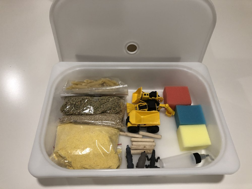 My sensory kit prototype. I ended up going with a smaller container and omitting the trucks because I couldn't get them on sale. Trucks are super fun in this sort of activity.