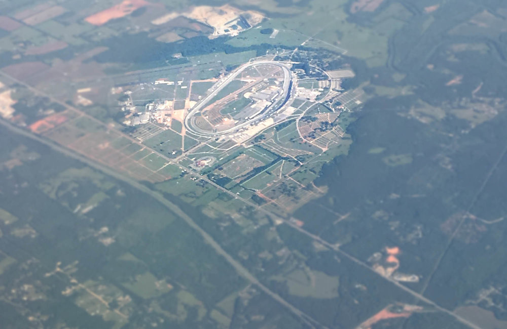 Talladega SuperSpeedway, all 2 miles of it easily stands out against the neighboring landscape.