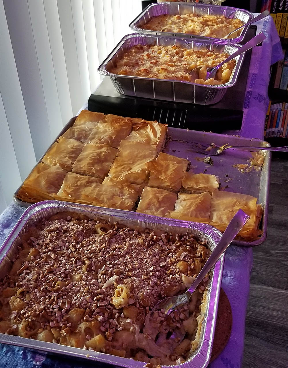 The German Mac N Cheese in the foreground with the pretzel topping along with Spanikoptia and two more Mac N Cheese pans at the top.