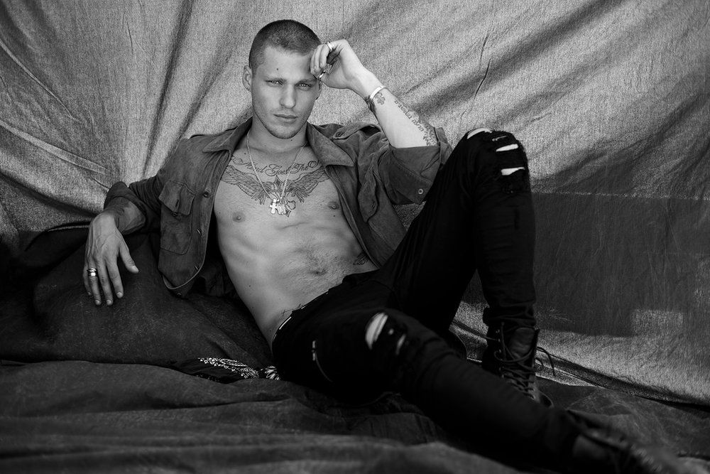 Russian model Vadim Ivanov lounging in ripped denim and open shirt for black and white fashion photoshoot
