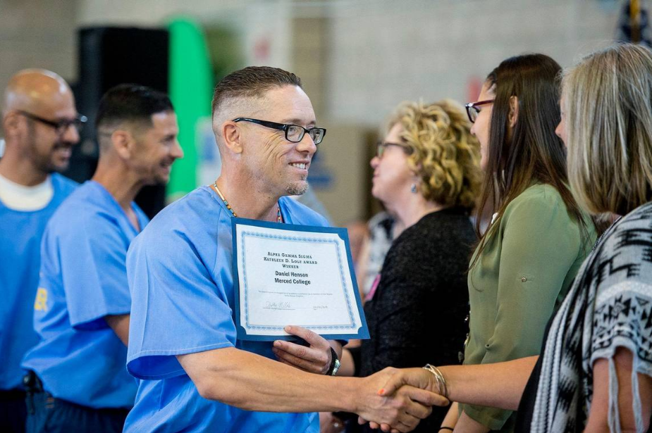 Inmate Daniel Henson, 37, left, shakes hands with Merced College professor Jennifer McBride after being recognized for receiving the Alpha Gamma Sigma Kathleen D. Loly award during a graduation ceremony at Valley State Prison in Chowchilla, Calif., on Wednesday, May 1, 2019. The ceremony recognized more than 60 inmates for their educational achievements including Associate of Arts degrees, high school diplomas, General Education Development certifications and those who have completed Career Technical Education programs. Andrew Kuhn AKUHN@MERCEDSUN-STAR.COM