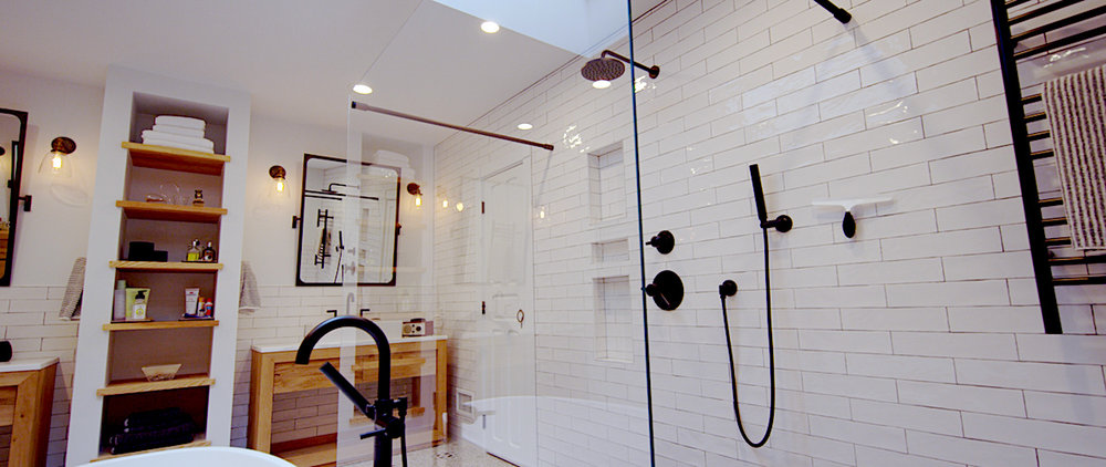 Statement Shower - Simple, yet dramatic. This frameless glass with handheld and rain shower heads will give you a new reason to sing in the shower. Black fixtures, alongside a black tiled floor add graphic touches of black to the simplicity of this space.