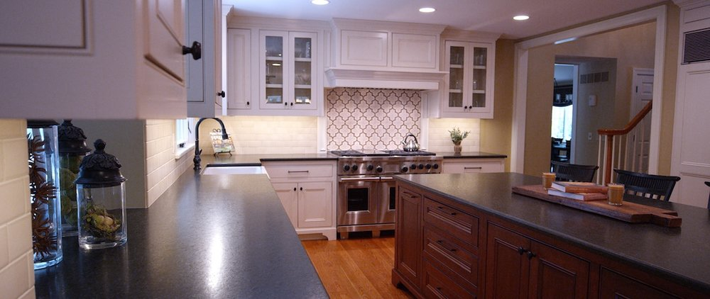 - Classic black and white present a timeless elegance, particularly with the wood-stained kitchen island. Decorative tile detail behind the deluxe range make it an incredible focal point for this kitchen. No need for takeout anymore. Cooking is a pleasure in this space, which balances trendy and traditional.