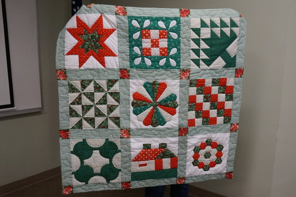 "- Tina's first quilt was a sampler made in 1990 when she was ""an unemployed newlywed."" The fabric was from her mom's stash."