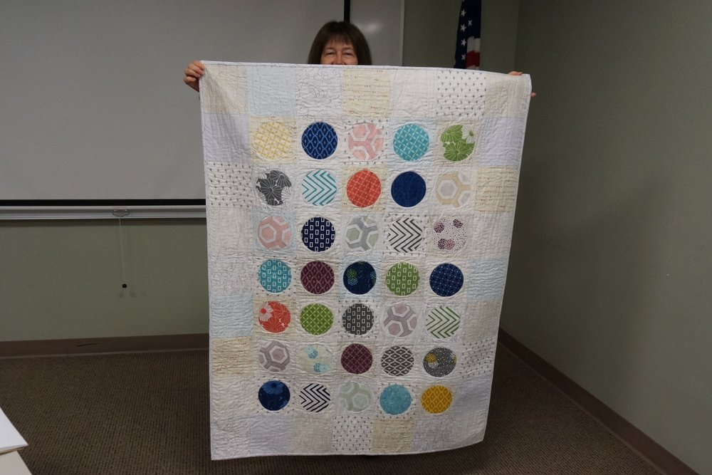 - Denise's latest quilt features charm square circles appliqued to a scrappy low volume background.