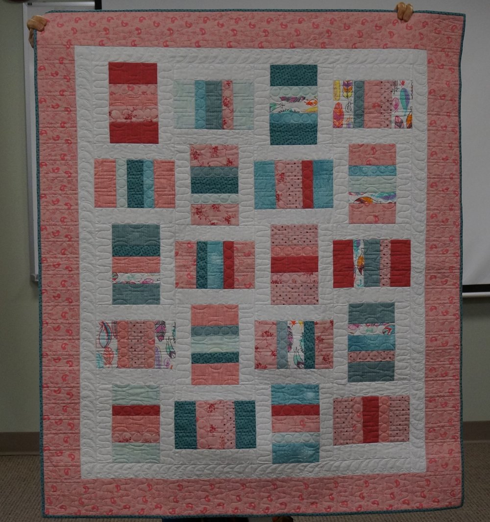 Celine made a quilt for a friend's baby, using fabric from the crib dust ruffle.