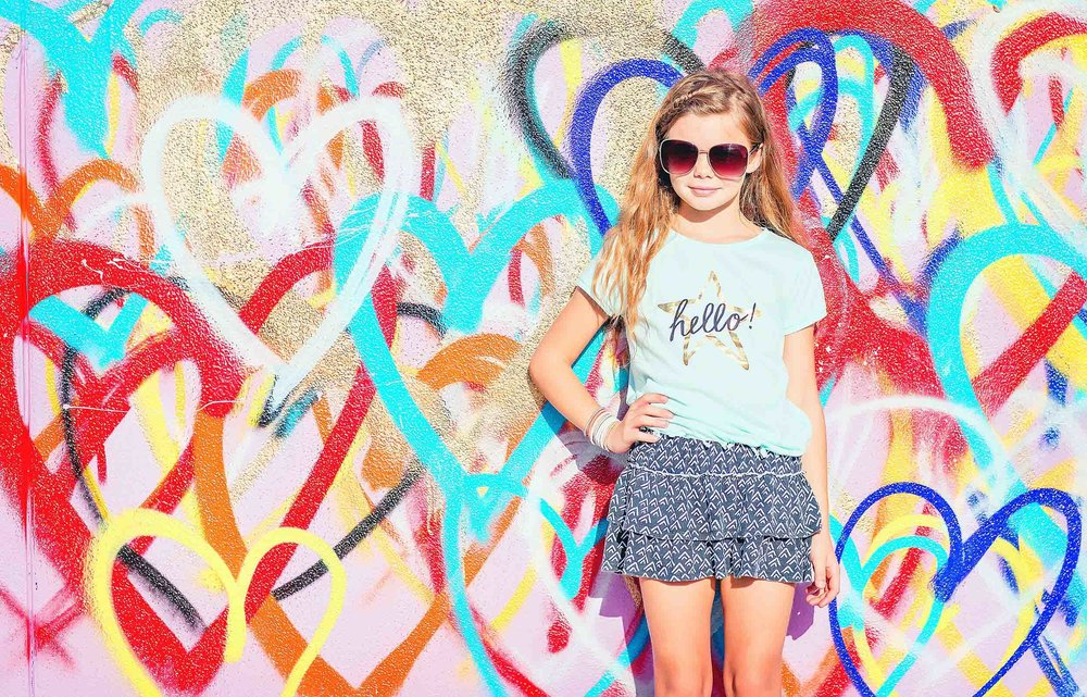 Colorful portrait of young girl against wall art in Houston, Texas.
