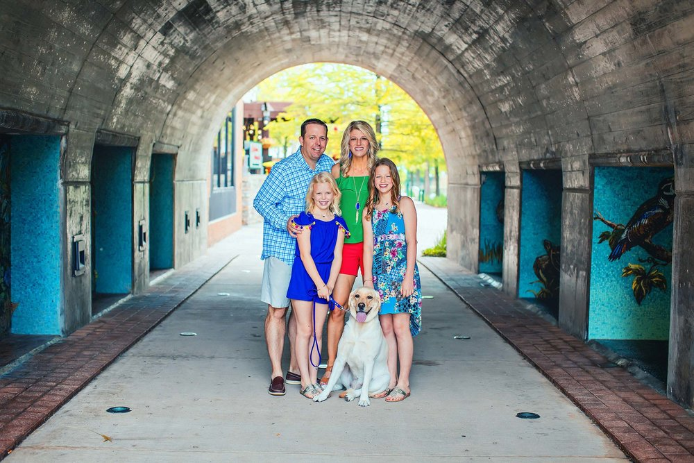 Portrait of family and pet dog in colorful clothes in The Woodlands Texas.