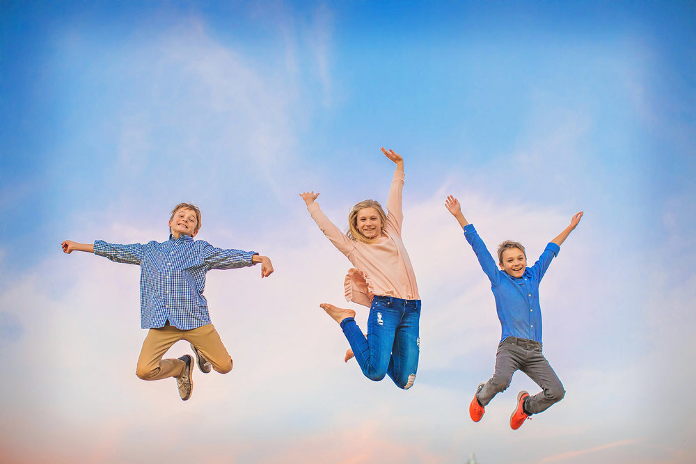 Tweens jumping in the dusky sky. Lifestyle portrait by spryART photography.