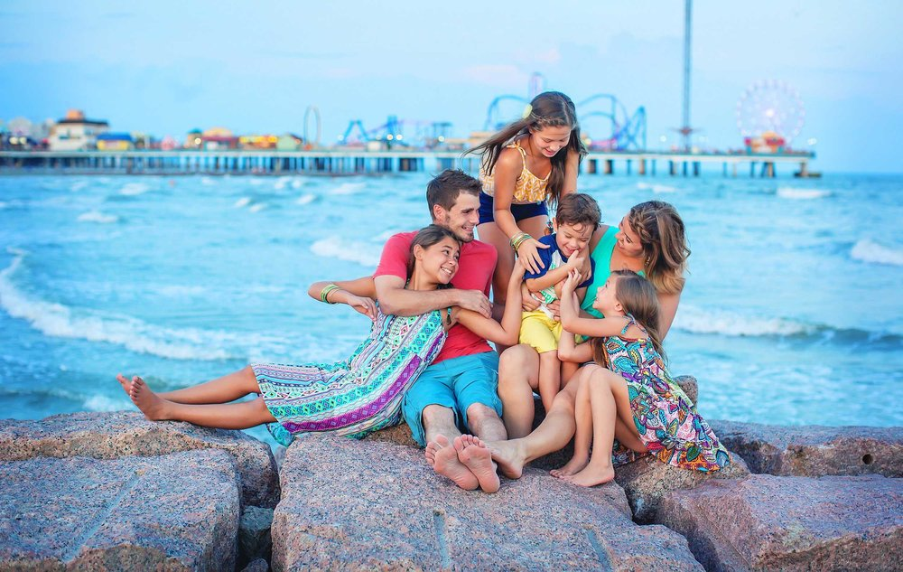 Lifestyle family picture in Galveston, Texas with Pleasure Pier in the background by spryART photography.
