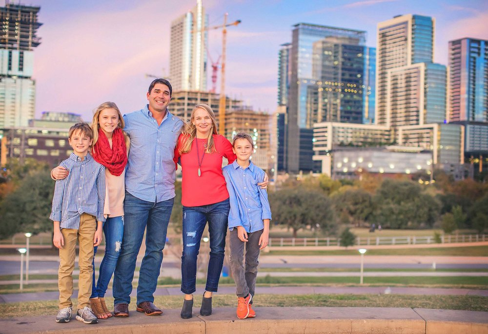 Family portrait at dusk with skyline behind them.