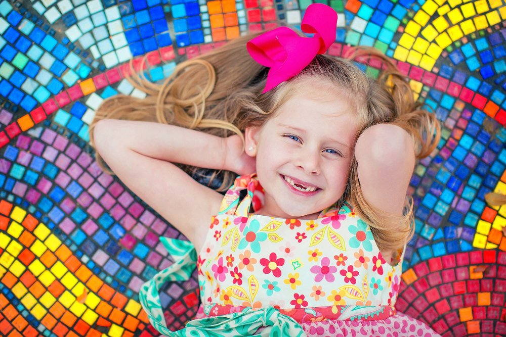 Colorful portrait of little girl laying on mosaic tile in The Woodlands, Texas by spryART photography