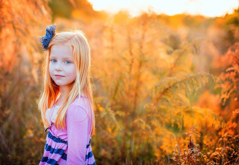 Portrait of red headed girl in field by family photographer spryART photography.
