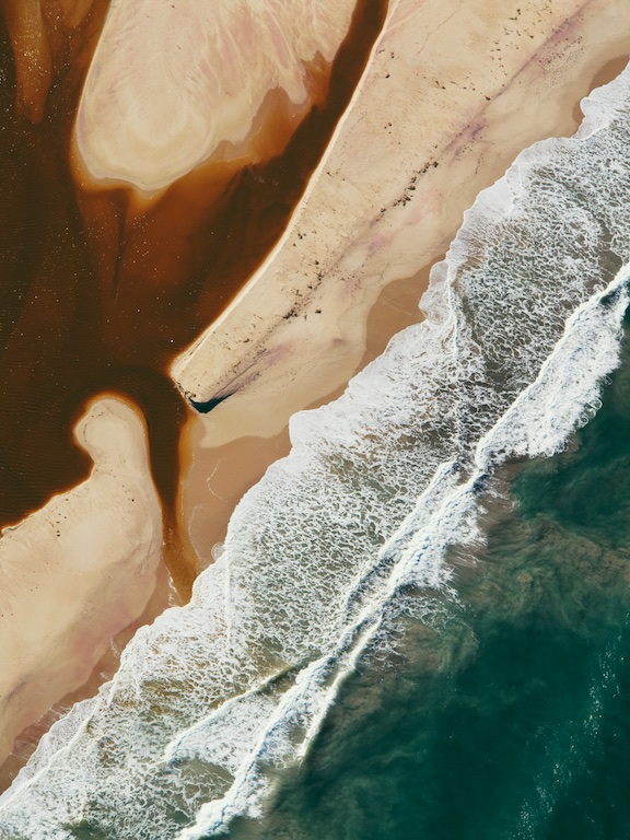 The mouth of the estuary at Greenough River, Western Australia, Australia.  The tannin stained river breaks through the sandbar and reaches the ocean.