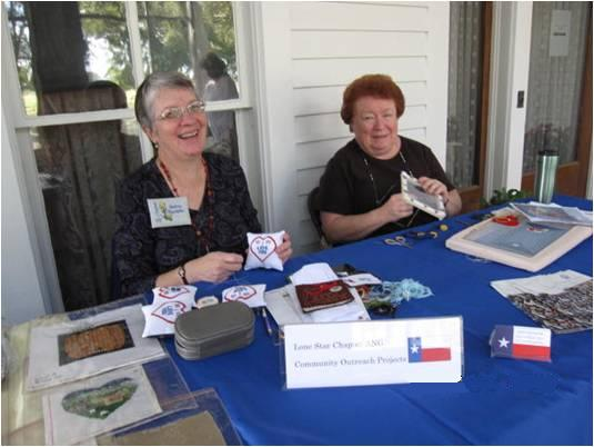 Andrea Standefer (L) and Linda Edney (R) stitch on the porch of the main house.