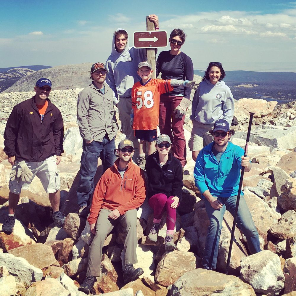 Volunteers install a new trail sign near Medicine Bow Peak.