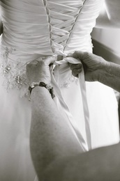 The beading is hand stitched back in place after the dress is taken in