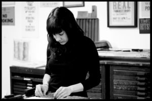 Sara hand typesetting a galley at her museum.