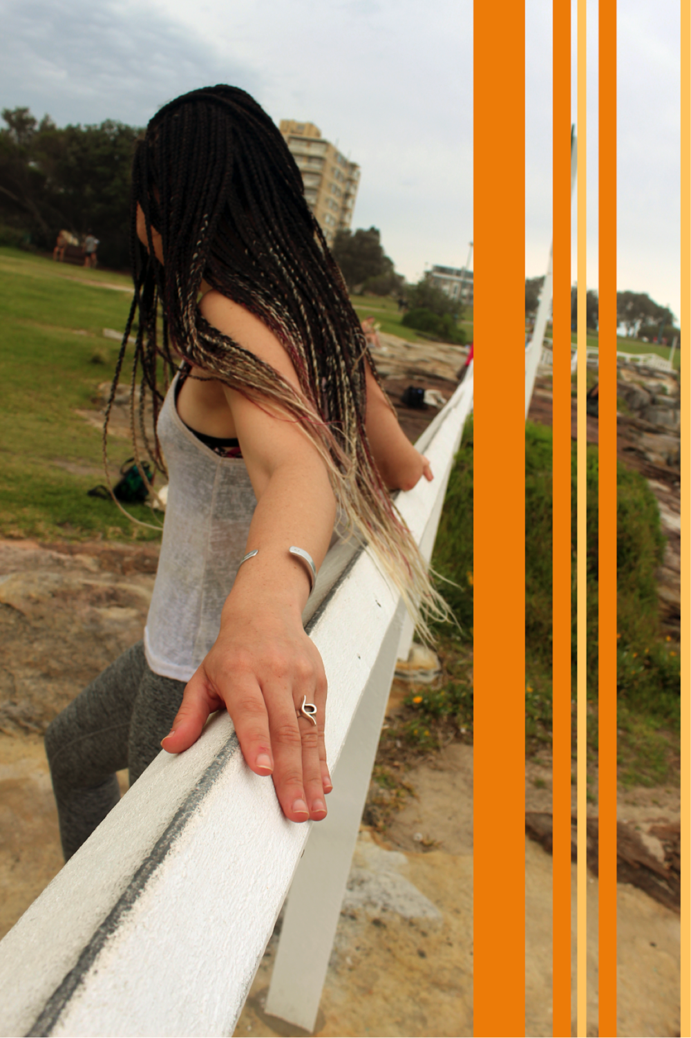 [image description: image of Ria leaning on a white fence taken from the side. You can clearly see a ring on her left hand, which has the eating disorder recovery symbol. She has brown braids which are magenta and blonde at the tips. There are orange and yellow vertical stripes on the right-hand side of the image].