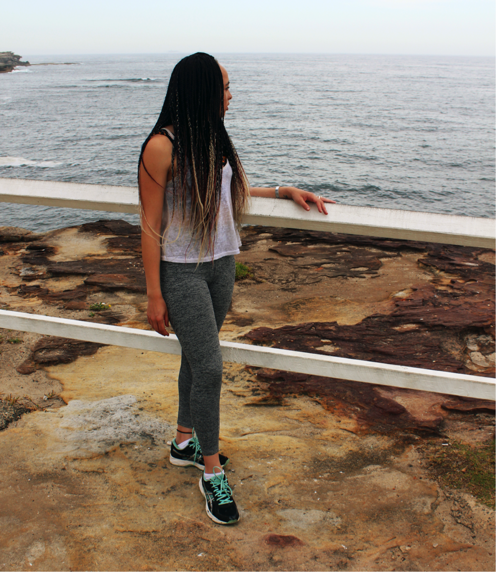 [image description: Ria in activewear standing on a rock and looking at the ocean over her left shoulder. Her left arm is leaning on a white fence and her right arm is by her side.]