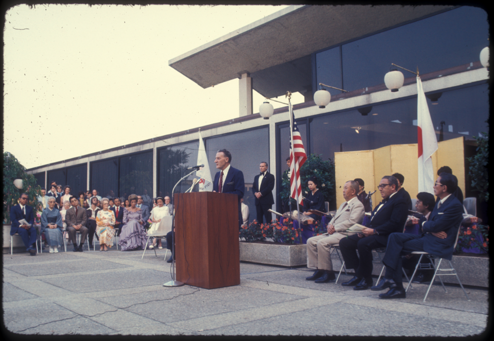 John Creech, Arboretum Director, speaks at the dedication ceremony for the Japanese Bonsai collection on July 9, 1976. Henry Kissinger, Secretary of State, is seated in middle at right.