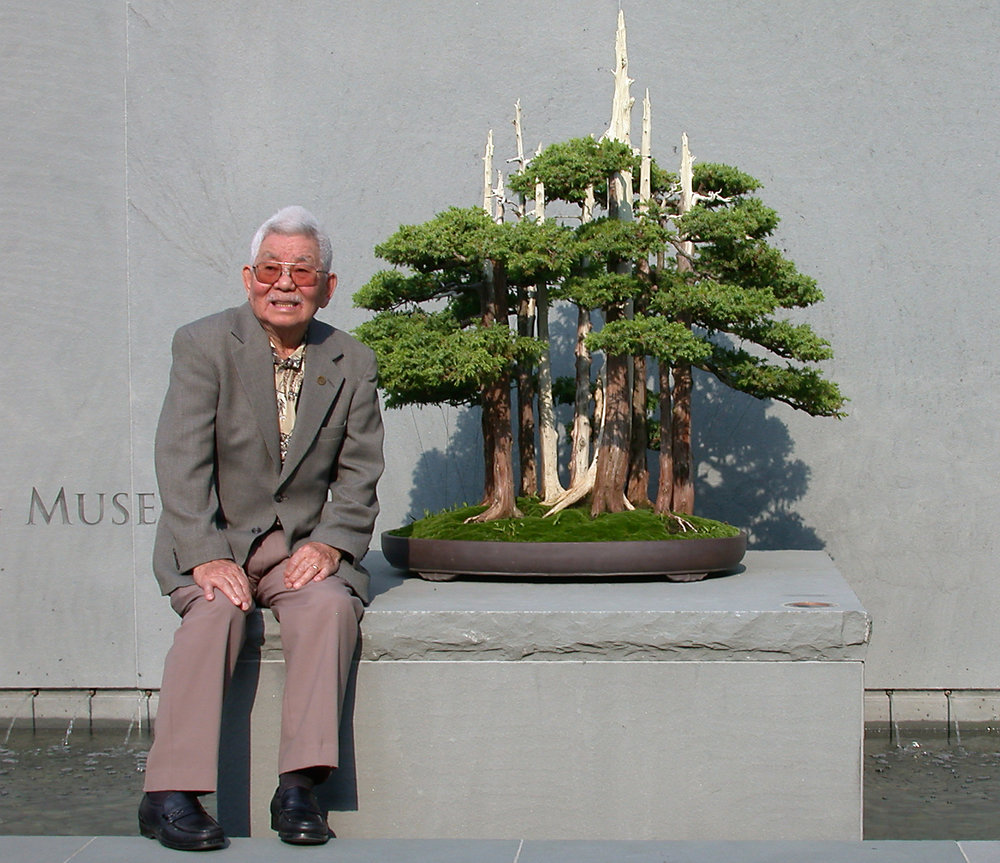 "John Naka pictured with ""Goshin"" at the entrance to the Upper Courtyard (2003)"