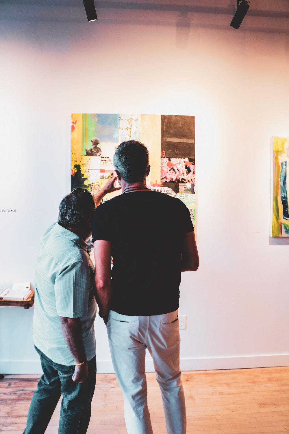 Two guests admiring a work by Mr. Mustart from the opening night of  Trials and Tribulations.