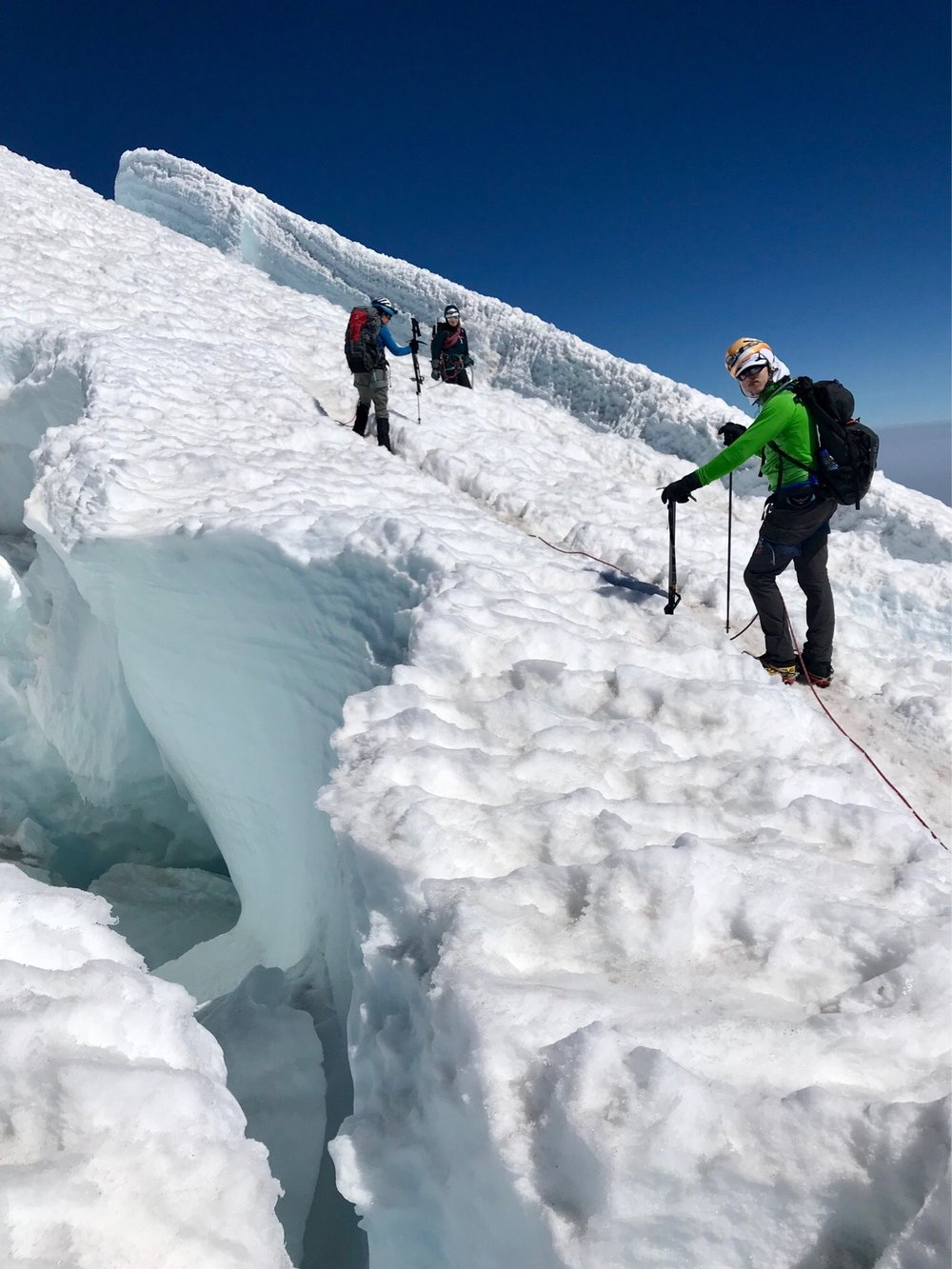 Liam stands next to a massive crevasse on Mount Rainier.
