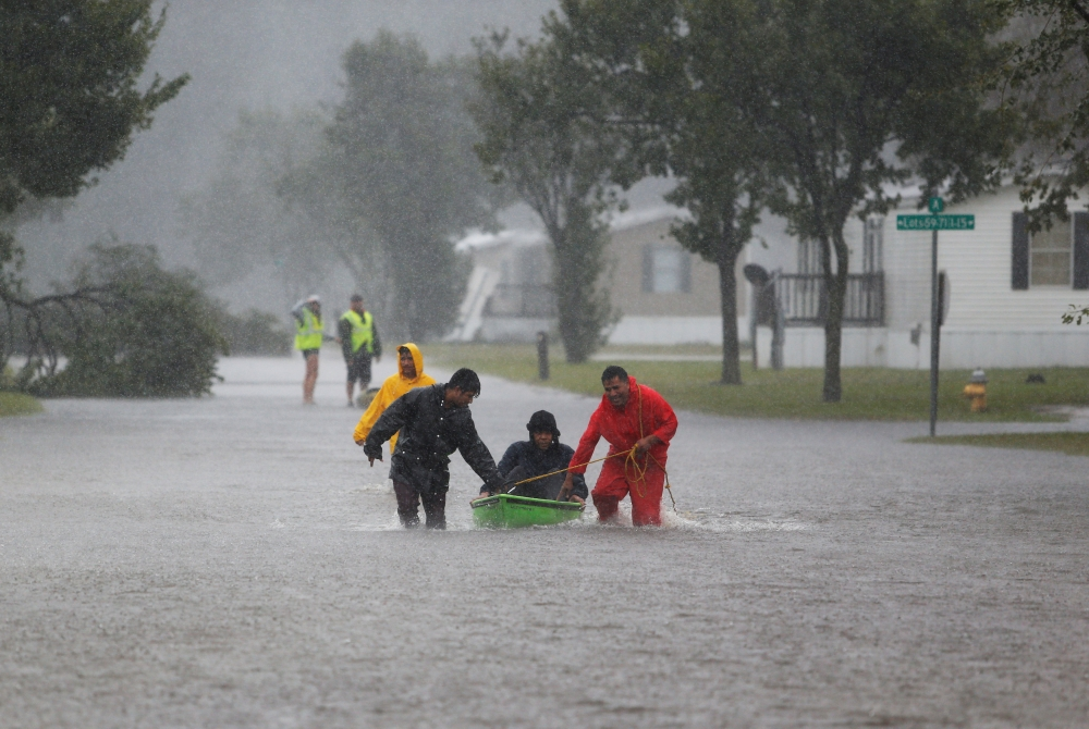 Residents help an elderly man evacuate a flooding trailer community in Lumberton, NC. (REUTERS: Randall Hill)
