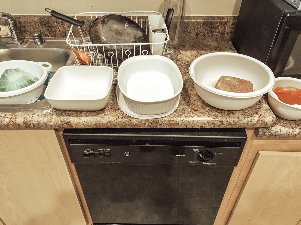from left to right: cabbage draining, empty bowl for cabbage leaves, final dish for baking, burger mix. tomato sauce mix.