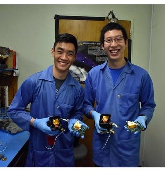 Aysen Tan and Ethan Tsai holding the two fluxgate magnetometers and their electronics delivered for flight