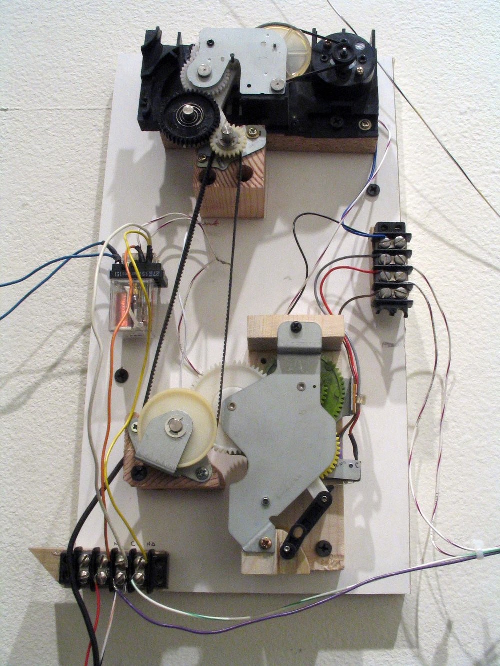 Some of the signals from the tattoo-machine-activated switch end up at this control board, whose assortment of scavenged gears translate the scattered on-offs into multiple signals with primitively configurable durations.