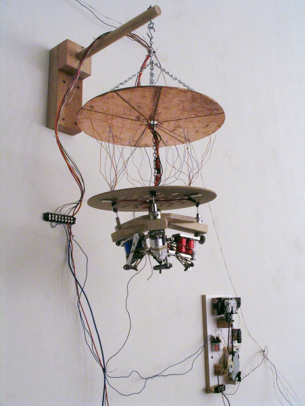 A self-generating chaotic switch. Upended tattoo machines vibrate the bottom plate and the attached wires. As the wires connect and disconnect from sections of the top copper platter, they send unpredictable on-off signals back to the tattoo machines and to other components of the installation.