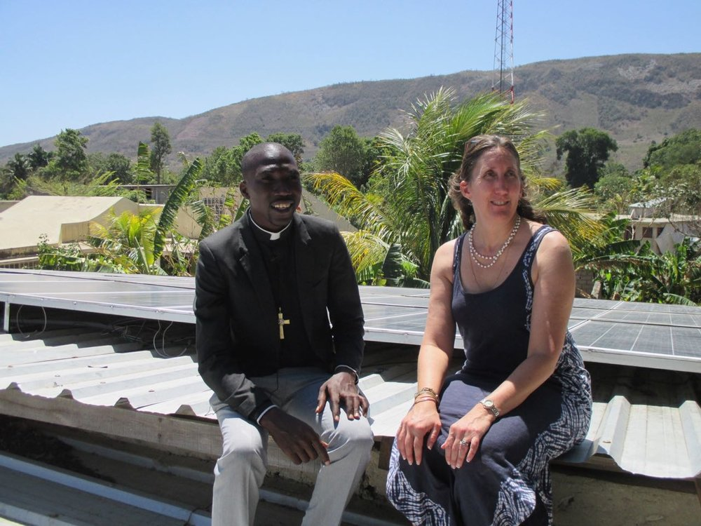 Deacon Schneyder Couloute and Dr. Delia Heck examining the 10 kWh solar system installed at St. Marc, Cerca la Source in March 2018.