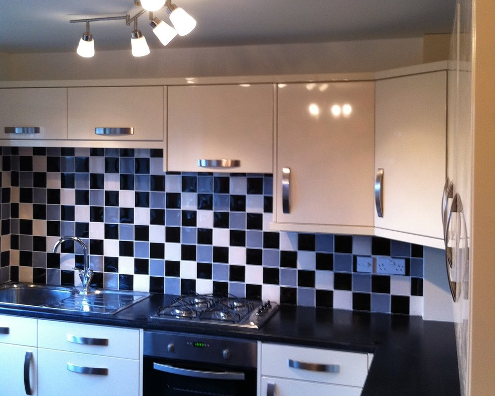 Cream kitchen with dark worktops and funky tiling