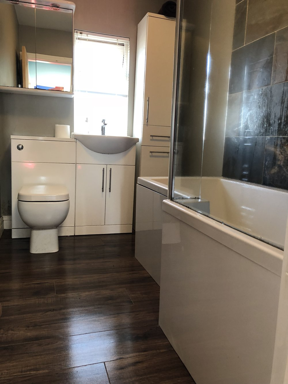 White bathroom suite with dark flooring and feature tiles