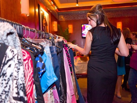 guest perusing donated clothing items destined for the women living in the care of the nonprofit, Women and Children First.