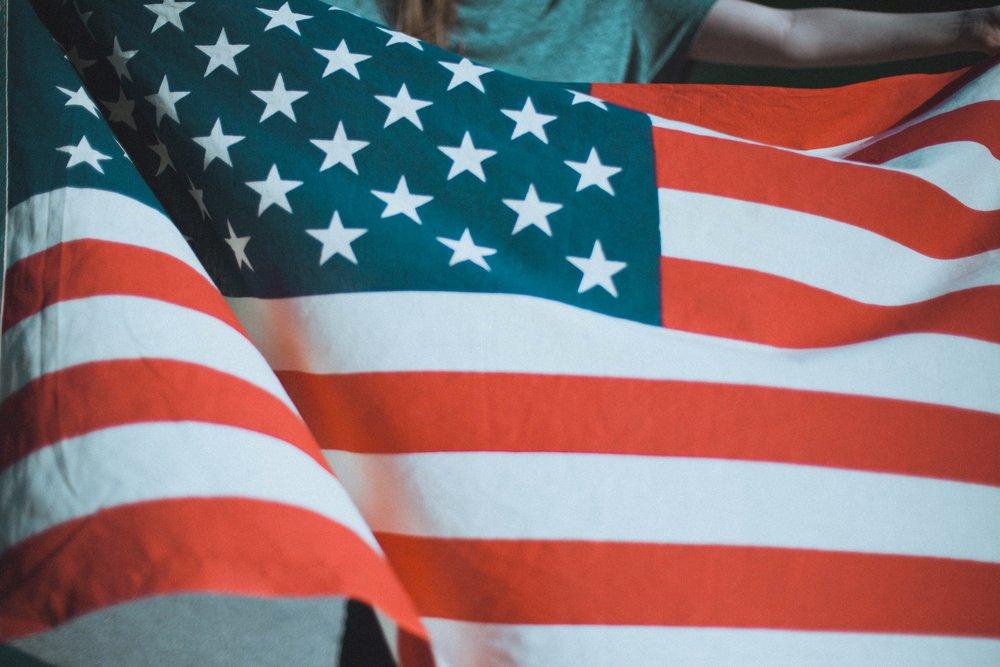 Female Veteran behind flag