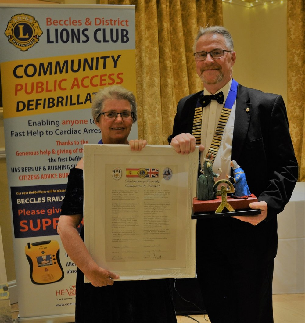 From Left to Right – Vera and District Lions Club President Pam Mattioli holding the Declaration of Friendship with Beccles and District Lions Club President Chris Ramsden holding the engraved gift received from Vera and District Lions Club to mark the club's twinning.