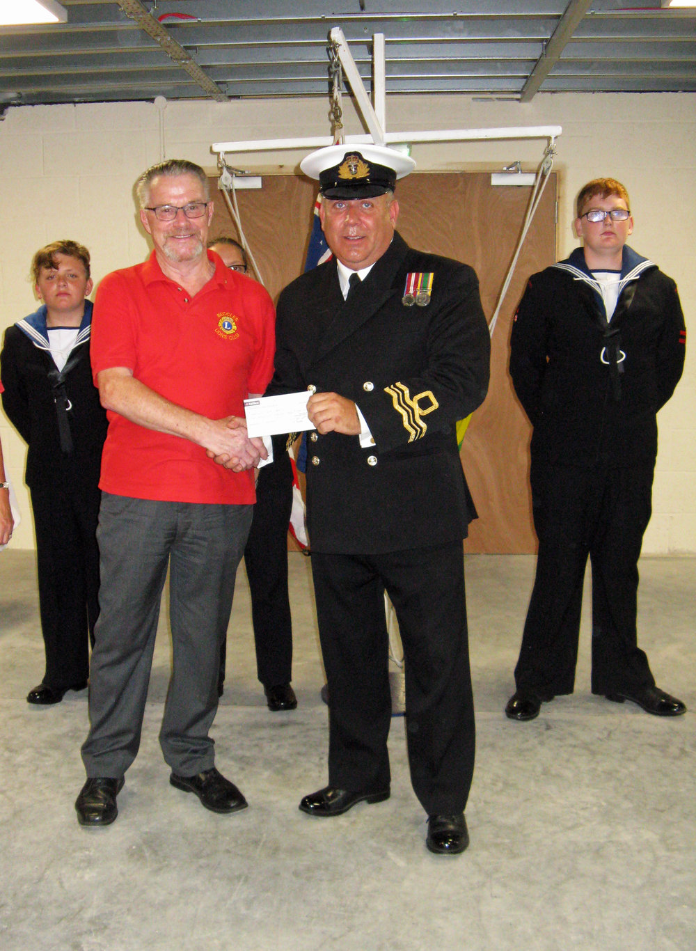 Lt.Cdr. Joe Meadows RNR thanking IPP Chris for cheque from Beccles Lions.