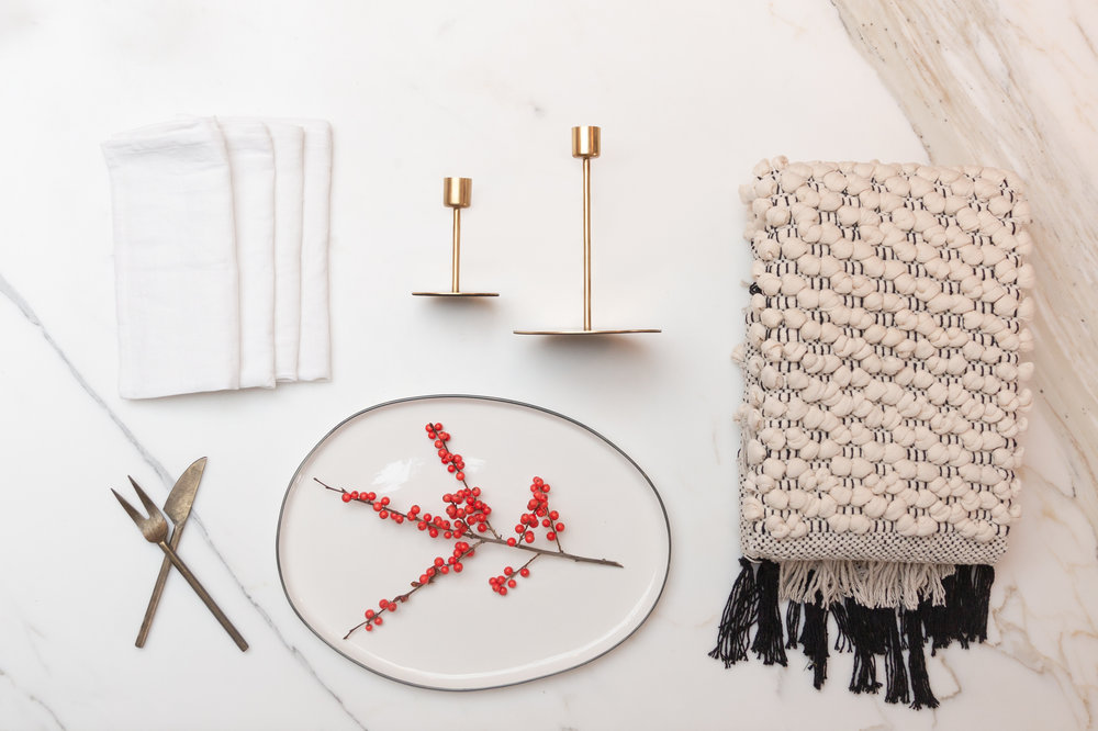 Cozy + White   ::  Gold Tapered Candlesticks :: Serving Platter :: Hand knit chunky cotton rug :: Bronze Serving Utensils :: Winter white linen napkins