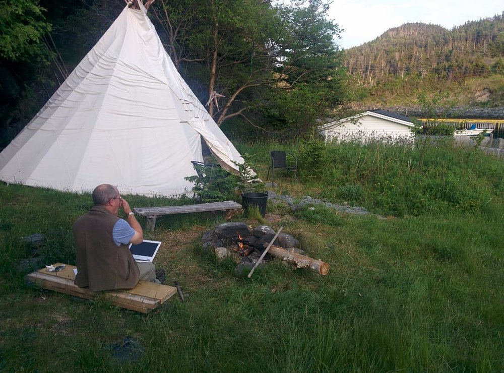 George sits at a campfire near the Teepee on a summer's night.