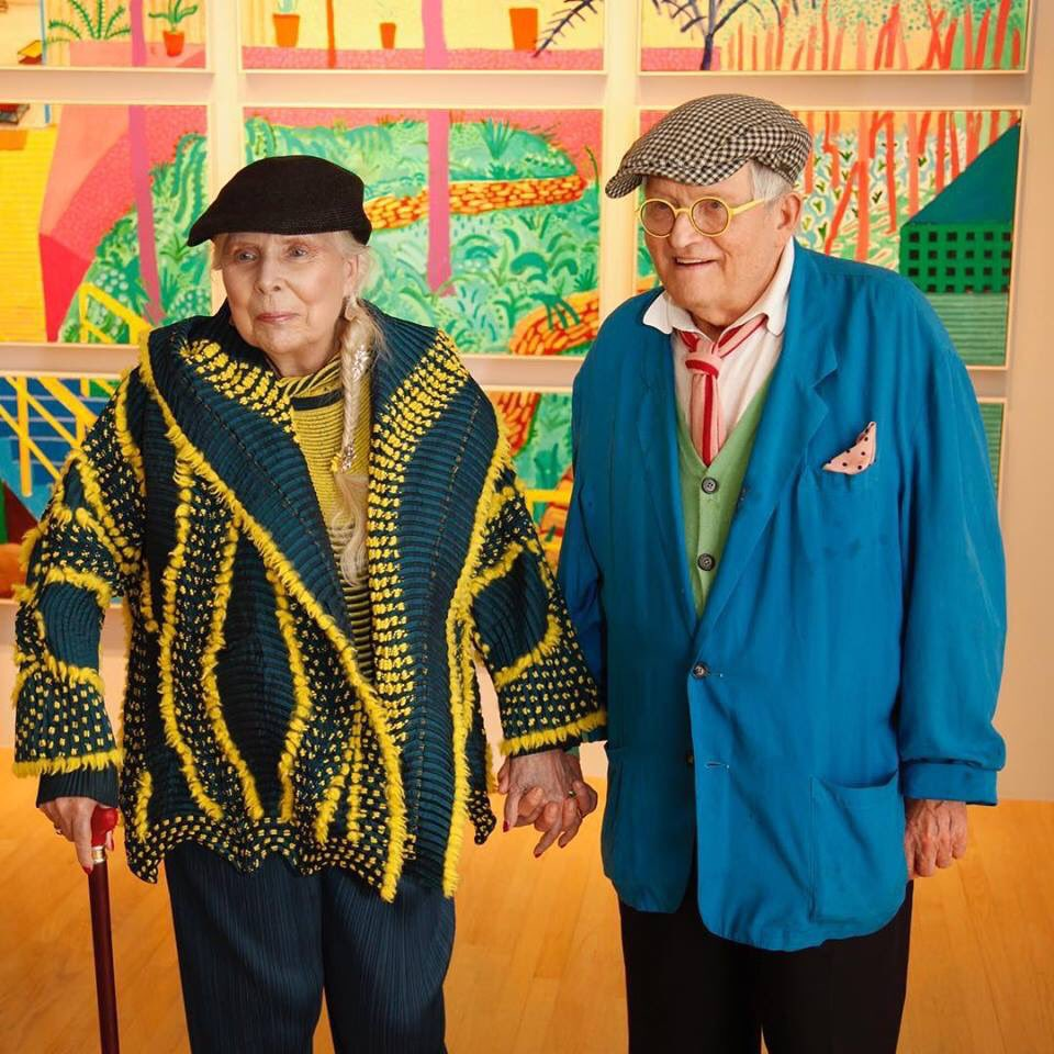 Joni Mitchell and David Hockney holding hands.