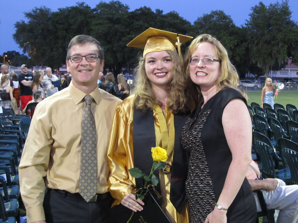 Wendy and her husband stand together with their daughter at her graduation. Wendy's daughter is dressed in gold graduation robes, and is holding a yellow rose.